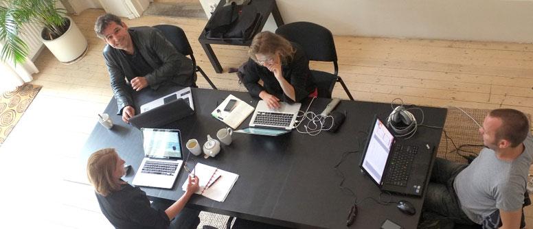 4 mensen om een vergadertafel, van boven gefotografeerd